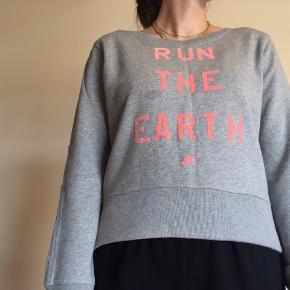"""Grå sweatshirt fra Nike med lyserød/ferskenfarvet tekst """"RUN THE EARTH"""" samt Nike logoet.  Har små detaljer ved ærmerne og er længere bagtil.  Perfekt til at smide på under/efter træning 🏃🏽♀️ Har en plet ved T'et, som måske er olie eller lign. som jeg ikke har kunnet få af ved almindelig vask.   100% bomuld.  Røgfrit hjem 🚭"""
