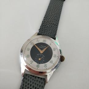 Super flot vintage ur med mekanisk urværk med manuelt optræk.   Uret er eftersigende fra 1960erne.  Mærket er Elsor. Urværket indeholder 18 juveler. Uret holder tid og går godt, men variationer kan forekomme grundet dets alder.   Mål:  Bredde inkl. Krone = 39mm Lug-til-lug = 45mm Tykkelse = ca 10mm  Uret har monteret en Hirsch rem som er brugt meget lidt.