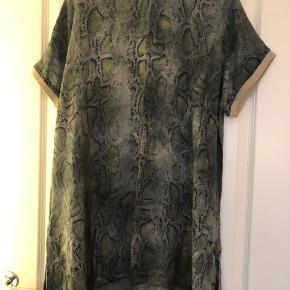 Fin tunika fra Lacony i grå snake, rib i ærmerne med lidt glimmer. Bm ca 2x32 cm Hel længde ca 83 cm lidt længere i siderne. 100% viskose Bytter ikke