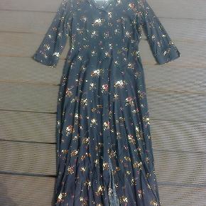 Varetype: maxi kjole med blomster maxikjole Farve: Brun  Kjole med knapper hele vejen ned foran.  3/4 ærmer 100 % viskose Sendes forsikret med dao mm andet aftales