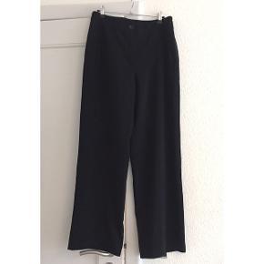 Sorte vintage bukser med høj talje og brede ben. Lukkes med knap og lynlås, og har skrå lommer i siderne.  Sender gerne med DAO :)