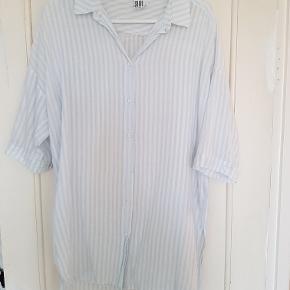 Lækker hvid/lyseblåstribet sommerksjorte med 3/4 ærmer. Lang model i 100% bomuld.  Mål Længde (foran/bagpå): 77cm/90cm Bredde: 56cm  Kun brugt et par gange, så er som ny,