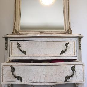 Fint lille sæt med kommode og spejl lavet i gammel stil med krakeleringer og guld-deko. Man kan godt se, det har været brugt, men det er også lavet sådan. Kommode: h65 b59 d32 cm Spejl: 44,5x70 cm Jeg tænker en samlet pris på 350-400 kr. Hentes i 3600 Frederikssund