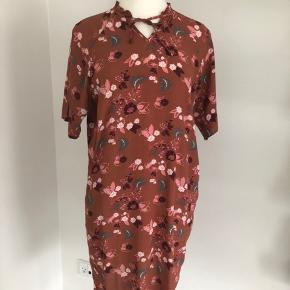 Soyaconcept kjole i rødbrun med korte ærmer og fine blomster i rosa, bordeaux og grå som motiv. Der er bindebånd ved halsen. Sød flæse ved halsen. Der er to forlommer. Længde fra skulder er 100 cm, brystmålet er 114 cm, og taljen måler 110 cm. Passer også str. M. Fremstillet af viscose. Bærer ikke præg af brug.