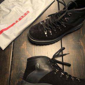 """Sælger et par Prada Hiking Boots i sort ruskind med læder. Exclusiv udgave lavet kun til Mr. Porter. Fremstår praktisk talt som nye.  Kommer med org. dustbag, kasse og kvittering fra Mr. Porter.  Befinder sig på Frederiksberg C, men sender gerne på købers regning.  Retail var omkring 6000kr  Mr. Porter skriver:  """"Exclusive at MR PORTER.COM Inspired by outdoor kit, Prada's hiking-style boots have been made in Italy from black suede and trimmed with supple leather. Rubber lug soles and substantial silver hardware enhance the rugged appeal, while padded collars and smooth linings ensure lasting comfort, even if you never leave the city limits."""""""
