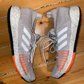 Adidas pulse boost HD løbesko. Lysegrå og orange detalje med sølv/metallic reflekser. Perfekt udendørs løbesko - god støtte. Brugt to gange. Lille flap ved striberne på den højre sko (se billede). Uden æske. Køber betaler for forsendelse - kan dog mødes efter aftale og handle på Amager for at bespare forsendelsen :)