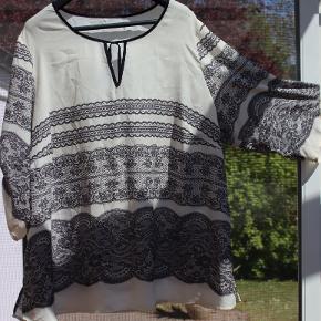 Str 52. Sort / hvid bluse med trykt mønster i 100% polyester. Lille v åbning ved hals samt bindebånd. 3/4 ærmer med sort strop for 'oprulning' (se billeder for begge muligheder)