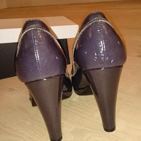 Heels i laklæder fra Marc by Marc Jacobs, str 38. Støvet lilla nuance med rosette foran. Prøvet dem udenfor rundt om huset, hvilket kan ses på lædersålen, men ellers ikke. * Bytter ikke *
