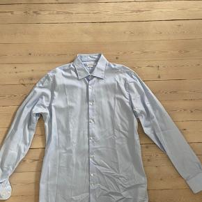 Pæn slimfit skjorte fra J. Lindeberg i str. 43 til pænt brug. Kun brugt 2-3 gange.  Bud er velkomne men bytter ikke.