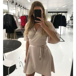 """En helt ny og sød """"Stella Wrap kjole"""" i champagne farvet fra design BYIC.  Nypris: 599 og er udsolgt   Bud modtages altid glædeligt i privat besked 💛"""
