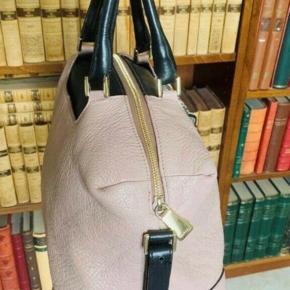 """Virkelig velholdt rummelig håndtaske (med skulderrem) i farven nude. Skindet har lidt grov struktur.   Tasken er ca 21 cm høj og 35 bred og 14 bred i siden.  Få brugsspor.  Sort foer.  Lukkes med lynlås.  En indvendig lynlåslomme.   Et udvendigt rum, hvor også den aftagelige hvid/grå """"pung"""" er monteret."""