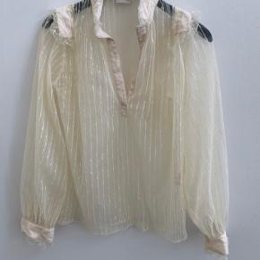 Super fin og let skjorte fra By Malene Birger str. 40 i flot creme/knækket hvid farve. Smukke flæse detaljer ved skulder og håndled.