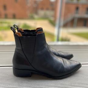Læderstøvler med lille hæl og spids snude. Læderet har ingen tegn på slid, men elastikker og sålen bærer præg af brug.