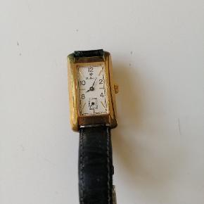 Mulberry ur i guld med sort rem. Uret er brugt og har slidtage.