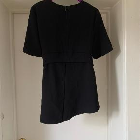 Black blouse, asymmetrical. Has a a belt coming from sides