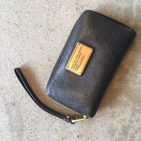 Marc by Marc Jacobs pung med guld logo. Pungen har 5 lommer til kort, en lomme med lynlås og 3 åbne lommer. Måler ca 9x15,5 cm.  Er brugt, men velholdt. Brugsspor ses på billeder.