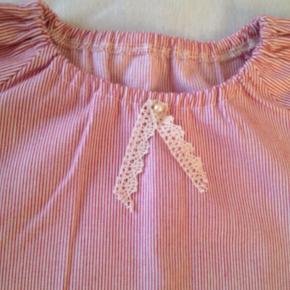 Den sødeste kjole med blondekant, brugt 1 gang som Julekjole til juleaften. Det er en str 116, men syet lidt kort, så vil sige at som kjole passer den bedst en 4-5 årig, men som tunika/bluse, kan den godt bruges til en str 116. Ærmerne er syet 3/4 lange.  Så skøn når den kommer på :)