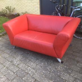 2 personers rød lædersofa, som har noget slidtage på sædet