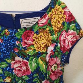 Vintage bomuldskjole med blå pailletter og blomsterprint i de flotteste farver. Lynlås bagpå. Hægte mangler. Pailletterne er lidt skrammede nogle steder, men stadig meget prangende kjole. Elastisk bomuld for et godt fit. Størrelse 10. Bytter ikke.