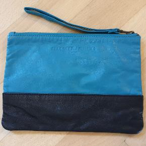 """Læder clutch fra Selected Femme 21 X 15,5 cm, lukkes med lynlås og har en lomme med lynlås indvendigt.  Der er et lille """"hak"""" i det sorte læder nederes, men det er ikke noget der ses.  Sender gerne."""
