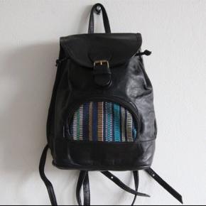 Håndlavet rygsæk i læder og håndvævet detalje på forlomme.  Lukkes med bindebånd og magnet.  Lille indvendig lomme.  Mål ca. 29x19x9