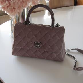 Prøv at se denne smukke sag fra Chanel.  Chanel Coco mini, dusty Pink. Med Rithenium hardware og Lizard top I caviar skind. Kun lavet en gang i denne farve.  Købt i august  2016 i Venidige ( alt følger med)  Jeg har købt tasken herinde i januar 2020 og ikke taget den i brug. Jeg har givet overpris for den, måtte bare eje den. Men af private grunde sælger jeg den igen.  Købs prise var omkring de 23.000 i 2016 Og Chanel stiger i pris hver år, og lignede takse i dag vil være meget dyrere.  Mål 22x15 målt nederst på tasken. Tykkelse 9 cm Rem 100 cm  Tasken er kun brugt få gange af tidligere ejer.  Sælges til 25.000 + gebyr eller via mobipay eller afhentning i Aarhus n  Ny pris i dag er over 28.000