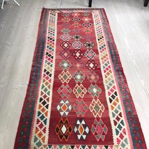 Fantastisk smukt kelim tæppe i røde og pink farver. Farven er løbet en anelse ud enkelte steder, men ikke noget man som sådan bemærker. Mål 120 x 275 cm.  Venligst se mine andre annoncer!
