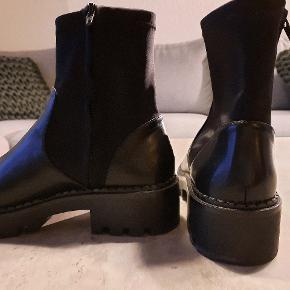 Støvler i imiteret læder. Skaft er i fleksibelt stof med lynlås i siden. Er gået med en enkelt gang, er for små. Tror muligvis de er lidt små i størrelsen.