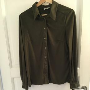 Skjorte fra OPM i mørkebrun. 100% polyester.