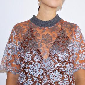 Flot t-shirt lavet i de flotteste blonder og med en fed kontrast krave. Længde : ca 60 cm Aldrig brugt!  Nypris : 300 kr  Køber betaler porto - ellers afhentes i København NV