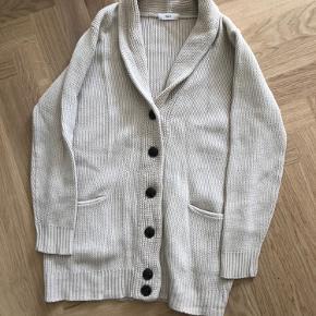 Cardigan/ striktrøje i ret tyk strik og en lys beige farve. Den er fin, men brugt en del, og sælges derfor billigt, selvom den ikke som sådan fejler noget.