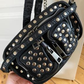 """Fed taske fra Nunoo i modellen """"Helena crossbody disco"""". Brugt en del, men den er i fin stand. Jeg har en iPhone 11 pro Max som der er fin plads til i det store rum.   Mødes gerne og handler og ellers sender jeg med dao på købers regning☀️"""