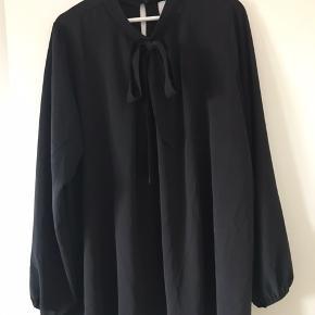 Sort langærmet bluse fra zizzi. Elastik ved ærmerne ved håndleddet, knaplukning bagpå og bindebånd foran til sløjfe.
