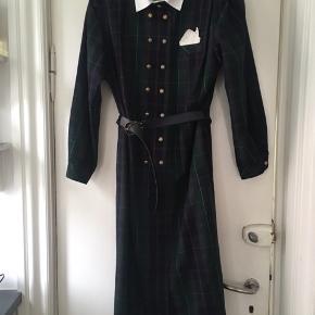 Super flot vintage - retro kjole i 100 % uld. Kjolen er i tip top stand og med meget fine detaljer. Sælges, da den desværre er for stor til mig. Størrelsen er en 42. Mål: længde 116 cm. Bryst 2 *50 cm. Talje: 2 *50. Taljen kan justeres med bælte.