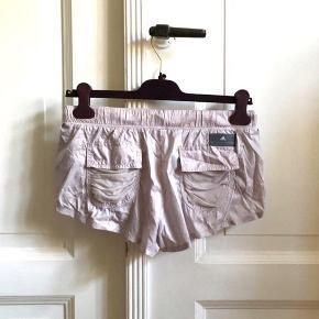 Feminine korte shorts fra Stella Mccartney adidas, der også kan bruges over et par leggins og f.eks. give lidt ekstra varme om vinteren. I pæn stand uden huller, pletter, fnuller eller lign. En str. 36, men kan også bruges af en str. 34/XS .  Se også alle mine andre annoncer!   Varetype: Sports shorts løbebukser løb lyselilla korte mini sportstøj lyslilla lilla