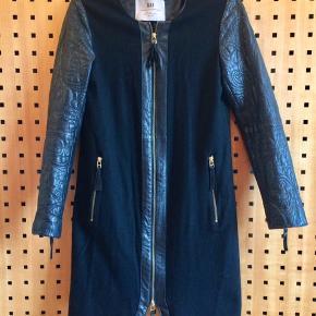 Lækker, velholdt sort uld-/skindjakke, som enten kan bruges som festfrakke eller overgangsfrakke forår/efterår.