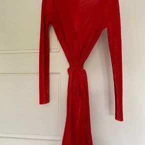 Rød slå-om kjole fra deviér med tynde plisseringer og langt bindebånd i taljen. Jeg har selv syet en lille trykknap i foran (se billede 3). (København Ø)  Jeg er åben for bud.