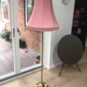 Smuk standerlampe med lyserød lampeskærm. Pære, der virker, medfølger. Ca. 155 cm. høj med lampeskærm på. Har patina men i flot stand