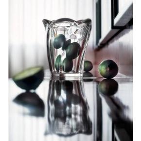 Smuk vase fra Holmegaards Galaxi serie, designet af sølvsmeden Allan Scharff, som har været tilknyttet Holmegaard Glasværk siden 1993. De skæve og lige linjer mødes i bunden og danner det samme mønster som i toppen, bare forskudt. Uanset fra hvilken vinkel, man ser den femkantede, asymmetriske form, vil den virke levende. Et smukt og tidløst stykke glas til enhver bolig. Højde: 17,5 cm Diameter: 9,5/15 cm