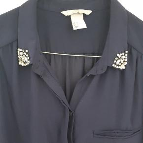 Flot skjorte i blå / lille og med sten på kraven  Fejler intet  Kom evt med et bud