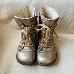 Skønne støvler med søde detaljer fra Angulus med uldfoer og såler i rågummi. Lynlås på indersiden, så de er hurtige nemme at få på. Metallic