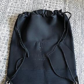 Varetype: Neopren taske Størrelse: 54x46 Farve: Sort  Fin neopren taske der lukkes med snore og kan haves på ryggen. Læder i hjørnerne og ret stor i str. 54x46 cm. Bytter ikke.
