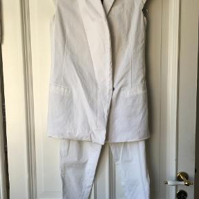 Hvidt jakkesæt i let køligt materiale. Brugt få gange. Så standen er praktisk taget som ny.  SE OGSÅ ALLE MINE ANDRE FINE ANNONCER MED EKSKLUSSIVE DESIGNERVARER!!!