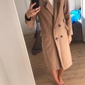 """Beige frakke i 100% uld.  Nypris: 2700 kr  Frakkens farve er lidt slidt et par steder (se billede). Det er dog ikke noget, der ses på afstand. Jeg kan forestille mig, at en rens tage det. Men derfor er standen sat til """"god men brugt"""".  Frakken skal afhentes i København, da den er tung at sende. Jeg bytter ikke."""
