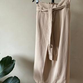 Nr 94  En virkelig fin asymmetrisk højtaljet nederdel fra Moss Copenhagen. Materialet er 65% Tencel og 35% bomuld. Farven er beige.  Byd endelig - og husk at tjekke mine andre annoncer igennem 😉  Vi kan mødes og handle i København ellers sendes varen med DAO på købers regning 🕊