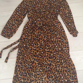 Brugt en gang og vasket.  Fin kjole fra Clothing By Ros i model Blomie (check flere billeder på deres hjemmeside). Kjole med fastslået slå-om, elastik i taljen og lille bindebånd. I fint materielle der falder pænt og ikke skal stryges. Størrelse M/L svarende til en 38-40.  Pris hos Clothing by Ros 259,- Sælges for 100 kr.