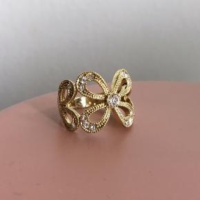 Helt ny ring med blomstermønster sælges da den er for stor. Jeg mener den er guldbelagt, men da jeg ikke er sikker sættes prisen ikke derefter. Den måler ca 2cm i indre diameter. Er du i tvivl om størrelsen, så mål diameteren på en ring du passer :-)
