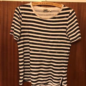 Lækker t-shirt i blå-og hvide striber med lidt 'farve-mangel' nogle steder.  Fin stand.