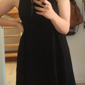 Ribbed sort kjole. Den har været vellidt pg er derfor brugt og vasket mangen gang. På et af billederne ser man et mærke fra en stearin-plet, men det er ikke særligt iøjenfaldende på afstand. Grunden til at den sælges er, at jeg bliver større, men det gør kjolen desværre ikke.