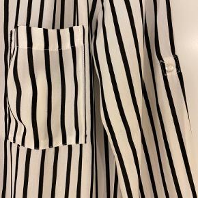 En rigtig fin og elegant bluse fra H&M i sort/hvid. Mulighed for at spænde ærmerne fast, så de fremstår som 3/4. Str. 36, men kan sagtens bæres af en M, da den er lidt løs. Brugt nogle gange. Næsten som ny.  Kan afhentes i Vejle eller sendes på købers regning.